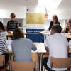 Debatující studenty pečlivě sleduje porota a přemýšlí o hodnocení.